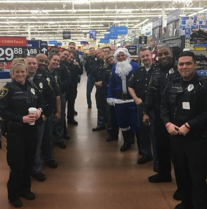 Officers line up to greet shoppers at Shop With Our Cops