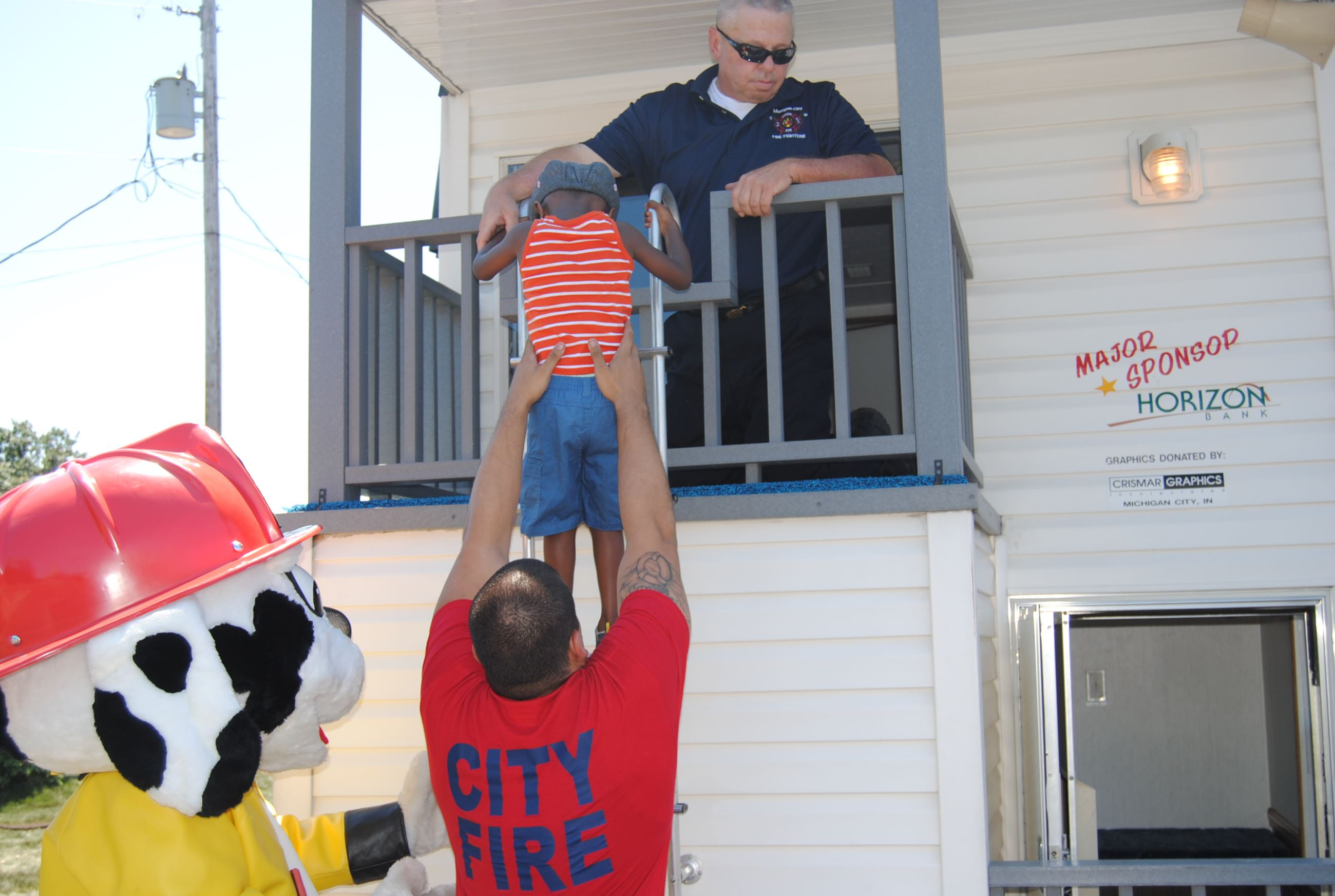 Firefighter lifts boy onto Fire Safety Education trailer