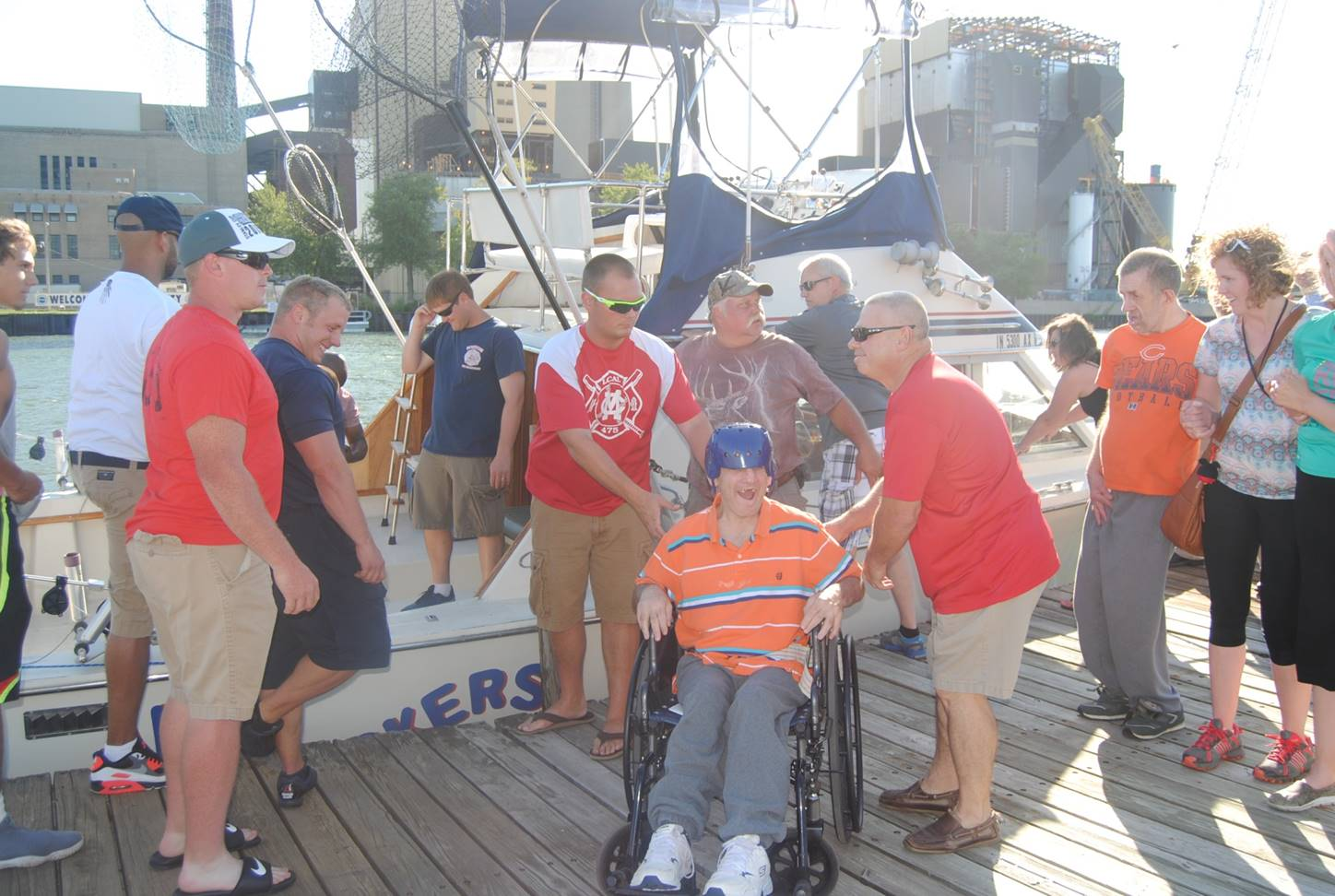 Firefighters assit a man in a wheelchair at the Abilty Boat Ride