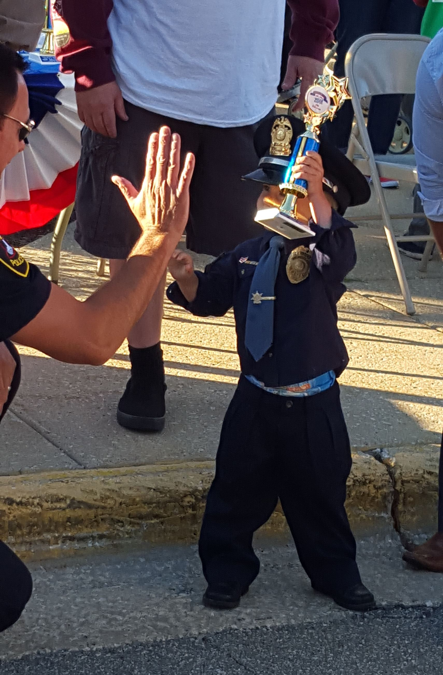 Little police officer gets a trophy from Chief Swistek in the Kiddie Parade